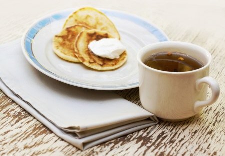 Breakfest set with tea cup and pancakes with cream on the plate photo
