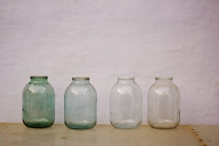 four empty old fashioned glass jars on the table