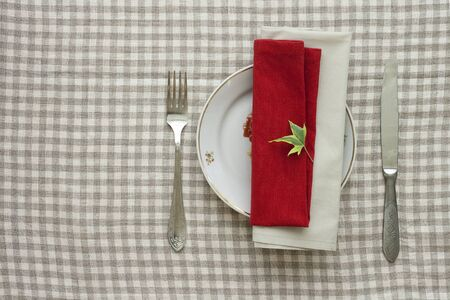 Lunch table appointments with plate, knife and fork on linen tablecloth photo