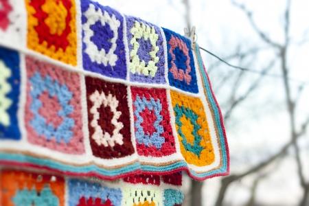 crochet: hanging handmade crochet blanket dry on air selective focus