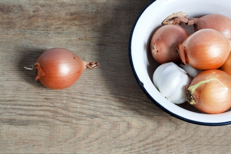 old fashioned still life with onion and garlic in enamel bowl on rustic wood