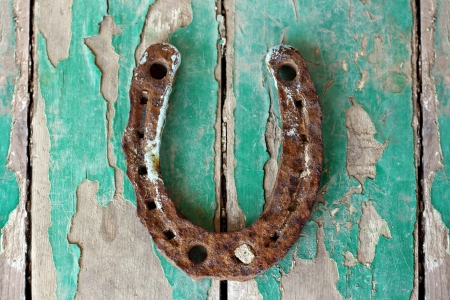 lucky charm:  antique rusty horseshoe on weathered green wooden surface