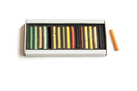 Box with pastel pencils on white background photo