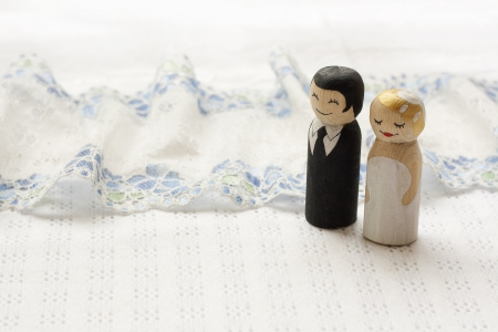 Bride and groome cake topper wooden doodle figures on white fabric background with laces Foto de archivo