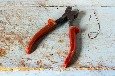 Used nippers with copper wire on rustic light blue wooden surface Stock Photo