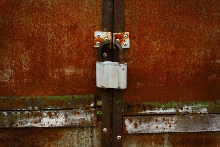 Rusty closed doors with old fashioned padlock Stock Photo