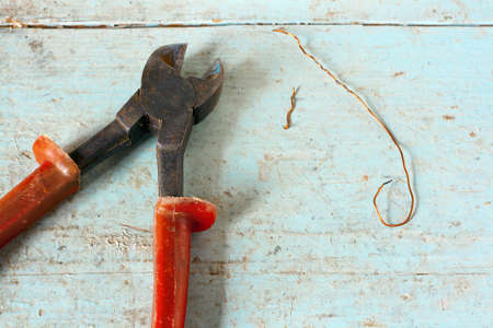 Used nippers with copper wire on rustic light blue wooden surface Stock Photo - 19283639