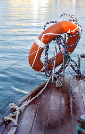 marina life: Orange life buoy in the yacht deck in marina