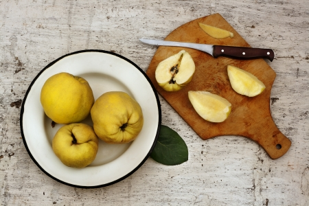 Rural still life ripe yellow quince fruits on the plate and cut fruit on plate with knife