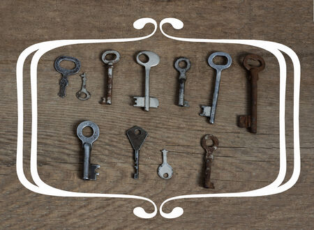 passkey: Old fashioned keys on wooden aged background with frame concept for text Stock Photo