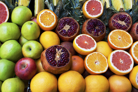 pommegranates: groseries shelf with fresh tropic fruits oranges, pineapple slices, apples and pommegranates Stock Photo