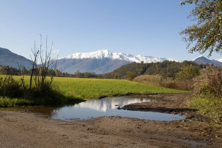Autumn landscape of green fields with snowy peaks of Alps in Colico town on the way to the Forte di Fuentes, North Italy.