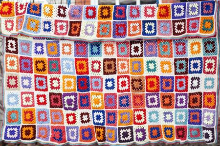 Colorfull handmade crochet blanket afgan made from woolen granny squares hanging outdoors on the string Stock Photo