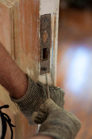 Locksmith use old screwdriver fix the lock on old wooden door Foto de archivo