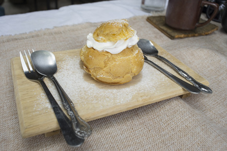 mouthwatering: Vanilla choux cream on wooden plate Stock Photo