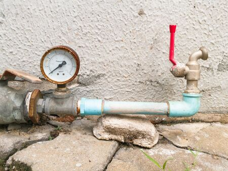 outside machines: Old and rusty pressure gauge and water tap installed in strange position