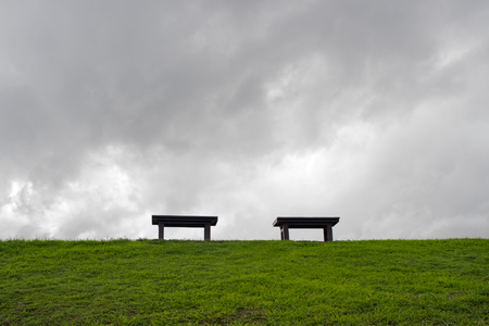grieve: Two benches in the center of green field with dark cloudy sky Stock Photo