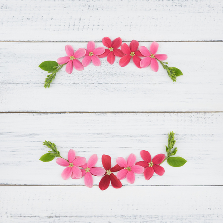 brightness: Wreath of pink and red flowers with green leaves on white wood background with copy space