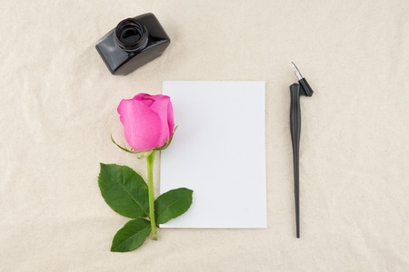 nib: Blank white card, oblique pen and bottle of ink decorated with pink rose on white muslin fabric with copy space