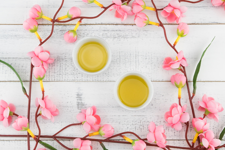 Cups of tea decorated with fake pink flower branches on white wood background