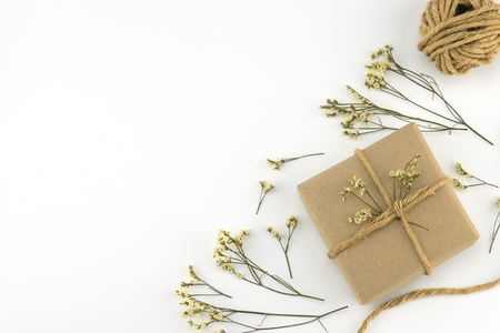 Brown gift boxes and rope with yellow limonium caspia flowers on white wood background with copy space Stock Photo