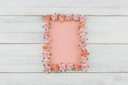 Blank pink card decorate with pink rose paper flowers on white wood background