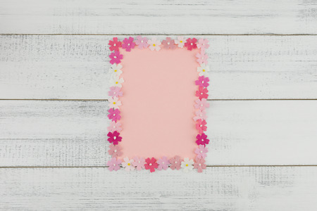 Blank pink card decorate with pink paper flowers on white wood background