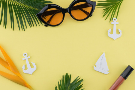 Sunglasses and lip gloss decorate with tiny sailboat, anchor, bird of paradise flower and fern leaves on yellow background with copy space