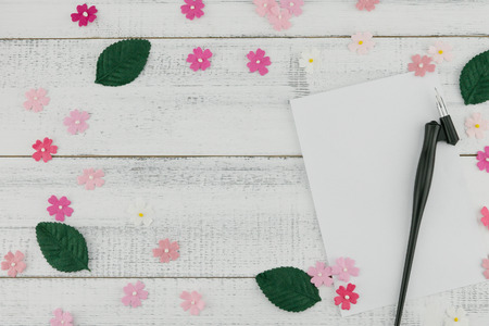 Blank white card and oblique pen decorate with pink paper flowers and green leaves on white wood background with copy space