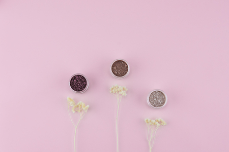 Glitter eye shadow set decorate with white dried flowers on pastel pink background with copy space