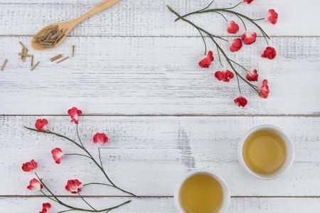 Thé et feuilles de thé sur cuillère en bois décorer avec des fleurs en papier rouge sur fond de bois blanc avec espace copie