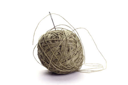 Coarse thread ball and needle on white background. Linen coarse gray threads and needle