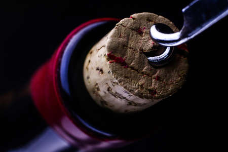 Corkscrew and bottle of wine.Opening of a wine bottle with corkscrew.Corkscrew and wine bottle on a dark background. Stok Fotoğraf