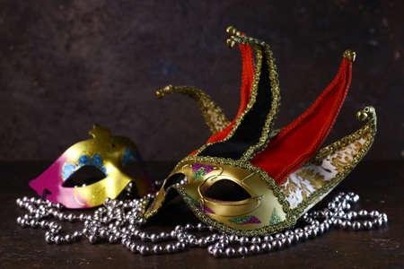 Carnival venetian Joker masks and silver beads on dark background. Carnival masks side view.