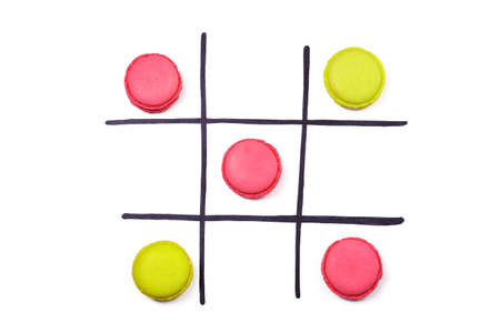 Tic-tac-toe. Different color macaroons and hand drawn black cells on white background. Logical game concept.