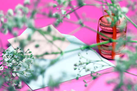 Pink macaroons with white open envelope and white wild flowers on pink background. Roman tic letter concept. Stok Fotoğraf