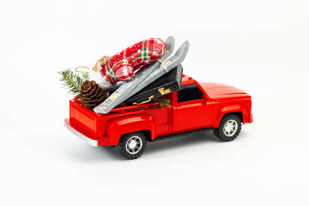 Winter holydays vacation concept. Red pickup toy with skis, gloves, suitcase, fir branch, fir cone in the trunk. Part of set Imagens