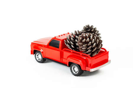Pine cones in red trendy pickup trunk. Toy truck and pine cones. Part of set.