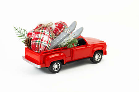 Winter holydays vacation concept. Red pickup toy with skis, gloves, suitcase, fir branch, fir cone in the trunk. Part of set.