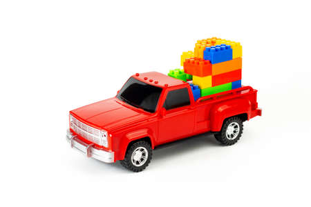Colorful cubes in red trendy pickup trunk. Toy truck and puzzles. Contemporary construction and development concept. Part of set.