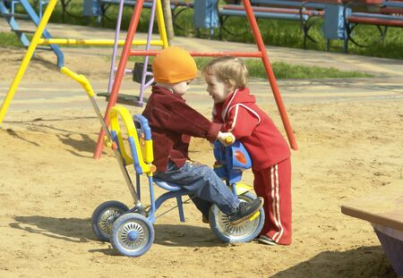 a boy on a tricycle and a girl near him                                Stock Photo