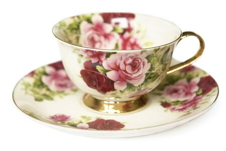 teacup on saucer decorated with gold and roses