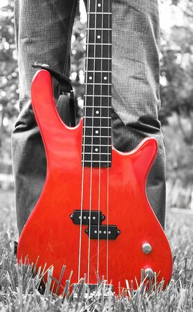 red bass guitar on the grass in black-and-white