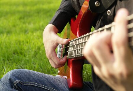 teenage boy playing the bass guitar on the lawn                                Stock Photo