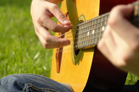 tune: young man playing on the guitar