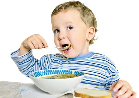 child eating soup isolated on a white background Stock Photo