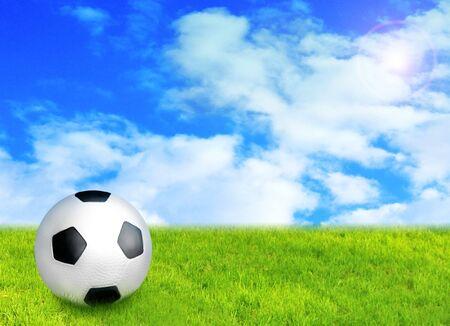 striker: football ball on grass against blue sky