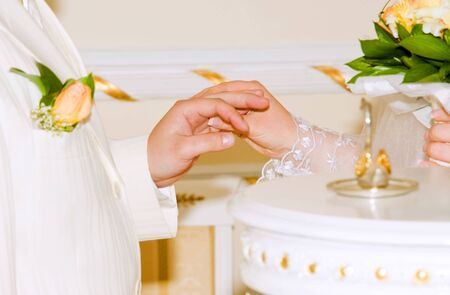 bride with a wedding bouquet puts on the gold ring to the groom photo