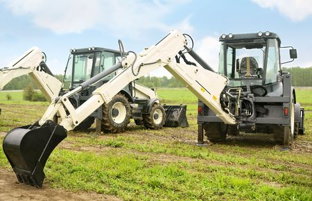 two modern excavators on the field