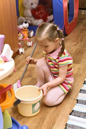 little girl cleaning the floor in her room
